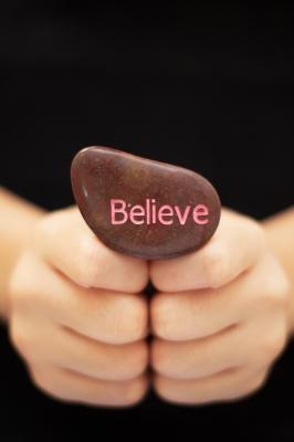 Hand Holding Believe Stone by thepathtraveler
